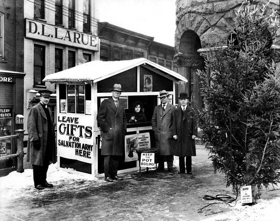 Salvation Army Booth in front of the First National Bank, Grafton, W. Va.  People stand outside the Salvation Army booth which is collecting gifts and taking donations for Christmas.