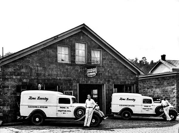 Two employees are standing in front of Home Laundry trucks next to a Dodge / Plymouth Garage in Grafton, West Virginia.