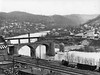 View into Grafton, West Virginia. Railroad tracks in foreground. There are bridges - St Marys is one being demolished, businesses, and houses along the river.