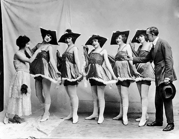 A young woman and a gentleman attend to five show girls posing for a group portrait.