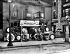 Three men standing outside in front of a Seiberling All Treads tire display at the Wolfe Tire Shop on Main Street in Grafton, W. Va.