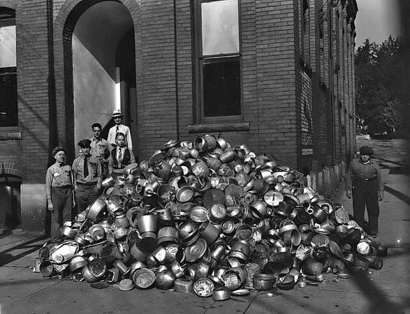 Group of people outside of Imperial Ice Cream Co. stand next to a large pile of tin buckets collected during a World War II Scrap Drive. Imperial Ice Cream Company Manager, Roy Z. Burnside, standing on top step.