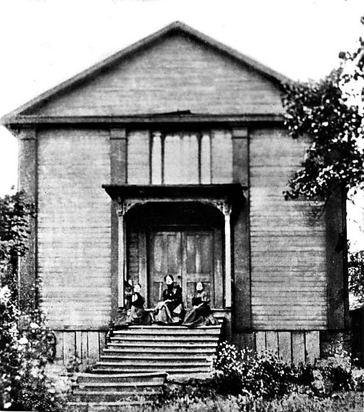 Three women seated on the steps of the wooden Catholic Church building in Grafton. Church was completed in May 1857 and dedicated in November 1857.
