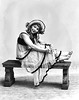 A woman wearing a dress and hat is sitting on a bench Grafton, WV 1916