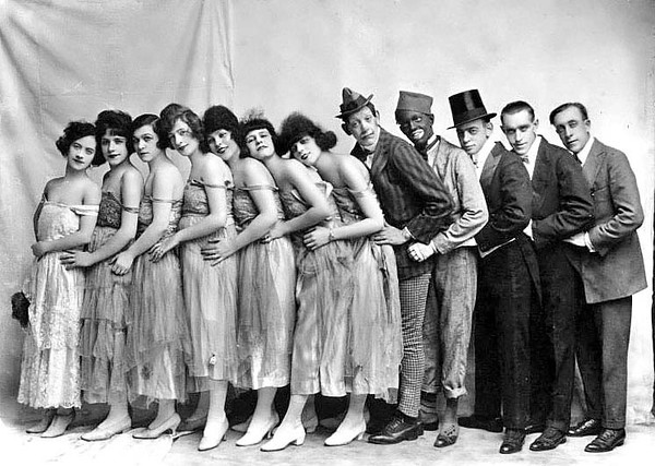 Seven female entertainers, two clowns, a man wearing a top hat, and two other male entertainers are standing in a line, Grafton, WV