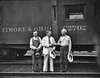 Three Baltimore and Ohio workers standing in front of a B & O train engine, Grafton, W. Va.