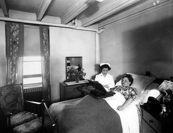 Woman lying in a hospital bed being attended by a nurse in Grafton, W. Va.