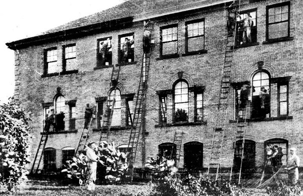 Cleaning Windows on a Building at the W. Va. Industrial School for Boys, Grafton, W. Va.<br /> Date ca. 1925