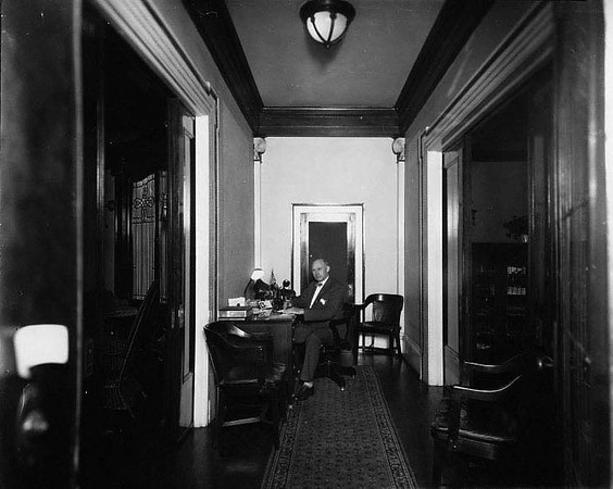 Interior view of the Bartlett home on McGraw Avenue in Grafton, W. Va. showing Col. Tom Bartlett working at his desk in the hallway.