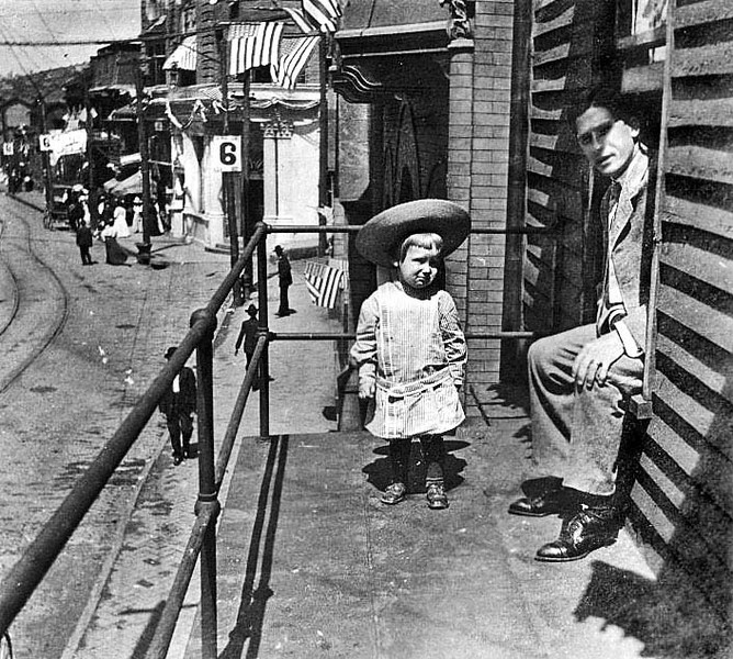 Man with a small child on a balcony overlooking Main Street in Grafton, W. Va.