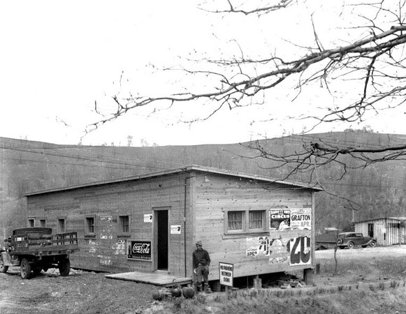Man leading against outside of old, wooden store in Grafton, W. Va.