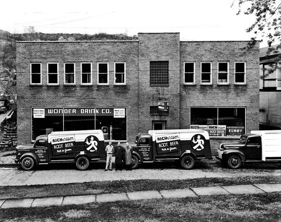 Three men are standing in front of two Richardson Root Beer trucks that are parked in front of the Wonder Drink Co., in Grafton, West Virginia.