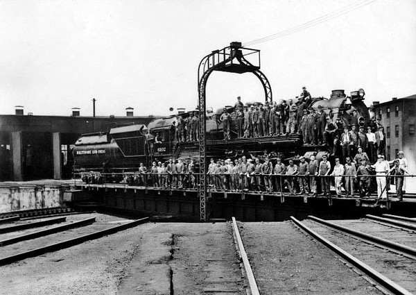 B&O Crew standing on a train engine while it's on a roundhouse turntable in Grafton, W. Va.