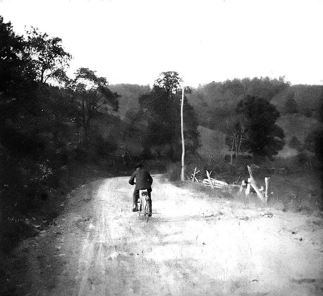 "Information included with photograph, ""View of Old North Western Pike before it was surfaced, just beyond the 'short turn'"". Pictured is Henry Wotney, a friend of Ada Haldeman, riding a wooden bicycle he made 1905"
