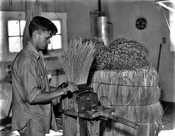 A man with a broom in a press at the Reliable Broom Plant in Grafton, West Virginia.