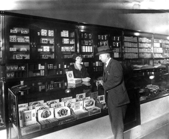 Interior view of C. G. Turner's Store in Grafton, W. Va. Man looking at cigars on top of a counter while woman attendant waits 1924.
