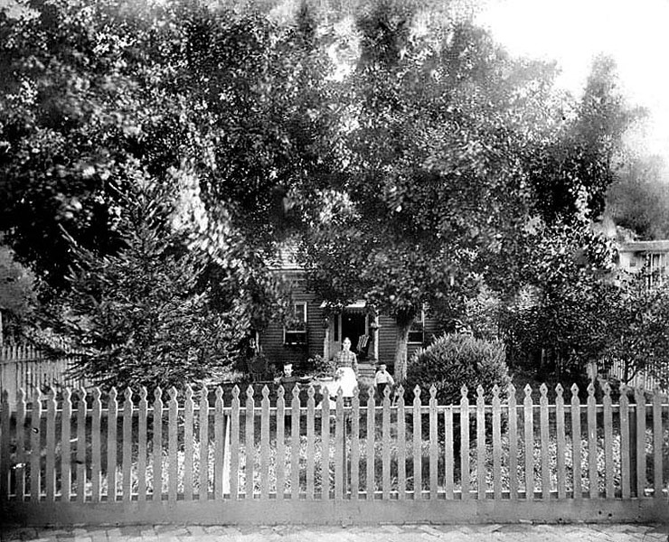 'First home of M. H. Dent and family--located on Front Street Grafton, W. Va., facing creek - at end of present South Side bridge. Mrs. Dent, Carrie & Herbert in foreground - unidentified girl at corner of house. Probably taken around 1885.'