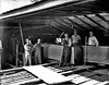 Workers at the Woodyard Lumber Company on West Main Street in Grafton, West Virginia. The photograph was taken in the shed as a log is being cut into boards. L to R: Ralph Woodyard (son of owner), Edwin Woodyard (son of owner), unidentified worker, Bill Woodyard (son of owner), and W. A. Woodyard, owner. The lumber company was owned and operated by the Woodyard family until 1990. The property was sold and the building was razed in 1992.<br /> CA: 1948