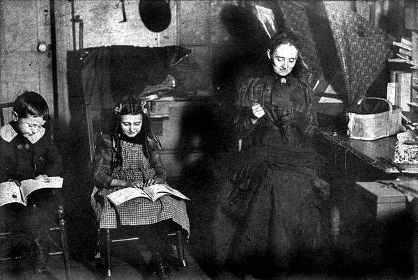 L.J. Loar Sr. and Grace Loar reading books, while Mrs. W.R. Loar is sewing, Grafton, WV 1900.