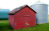 Pair of wooden red granaries on the Husak farm, with newly roofed quonset building in the background.