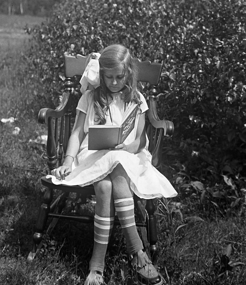 """About 1924:  My mom reading a favorite book, """"Chicks and Chickens.""""  This picture is from a glass plate negative.  photo by H.J. Flad"""