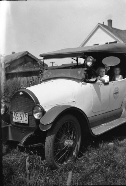"My aunt Louise ""driving"" a 1916 Willys Overland Model 75B Touring car.  That's my mom in the back seat.  Picture dates about 1918."