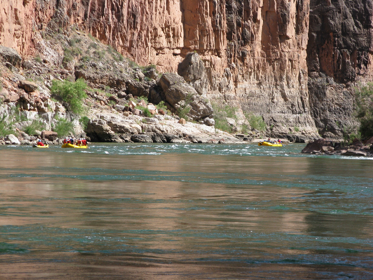 Small rafts and a kayak start through the rapid.