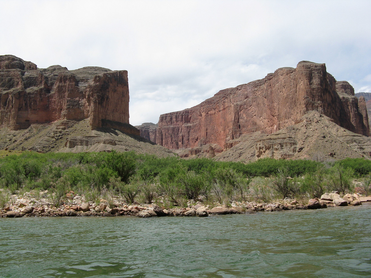 Mile 52.5:  Nankoweap Canyon.  On the left side of the picture, in the cliff just above the slope, are little dark areas which are openings to granaries.  These rooms stored grain for Puebloan people about 1100 AD.