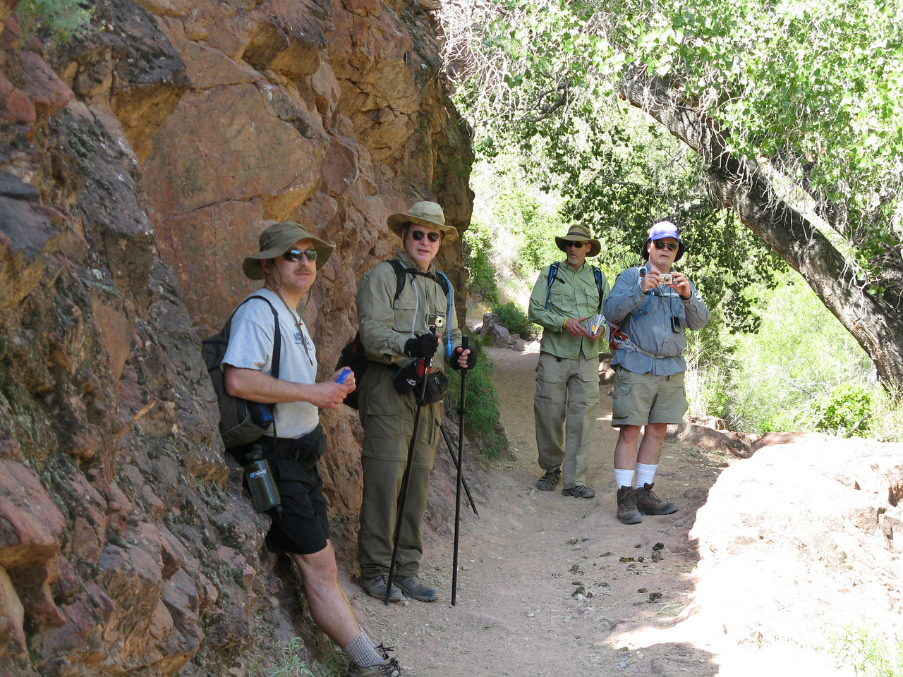 By mid morning, a rock face along the trail provides welcome shade. (L to R) Dairusz, Richard, Glenn, Wendell.