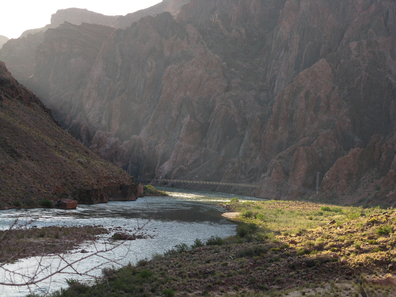 The sunlight begins to reach the river at the bottom of the canyon with the Silver Bridge in the distance.