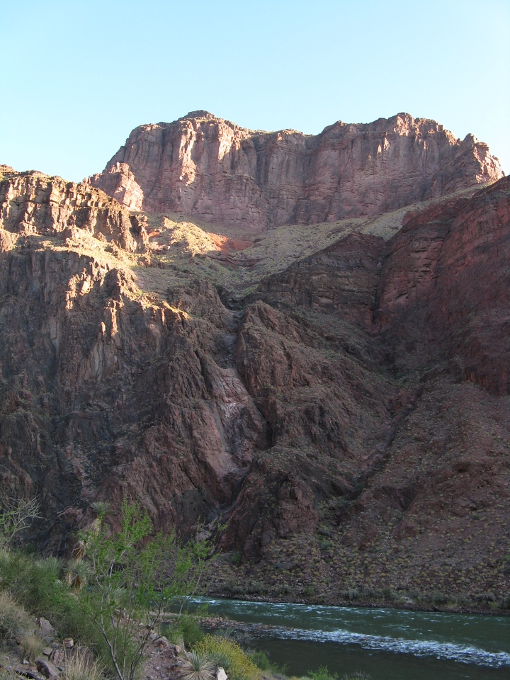 Looking north across the Colorado River, the rocks above are highlighted in morning sun.