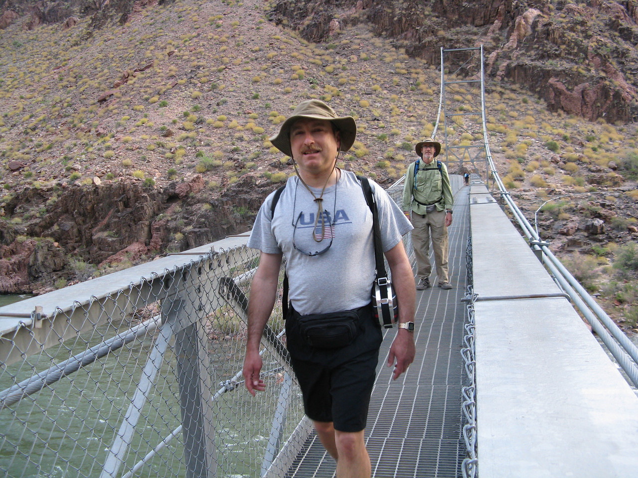 The Silver Bridge occurs at 0.7 mile from Phantom Ranch and 2450 feet of elevation above sea level.<br /> <br /> On the Silver Bridge, Dariusz and Glenn are walking towards the south side of the river.