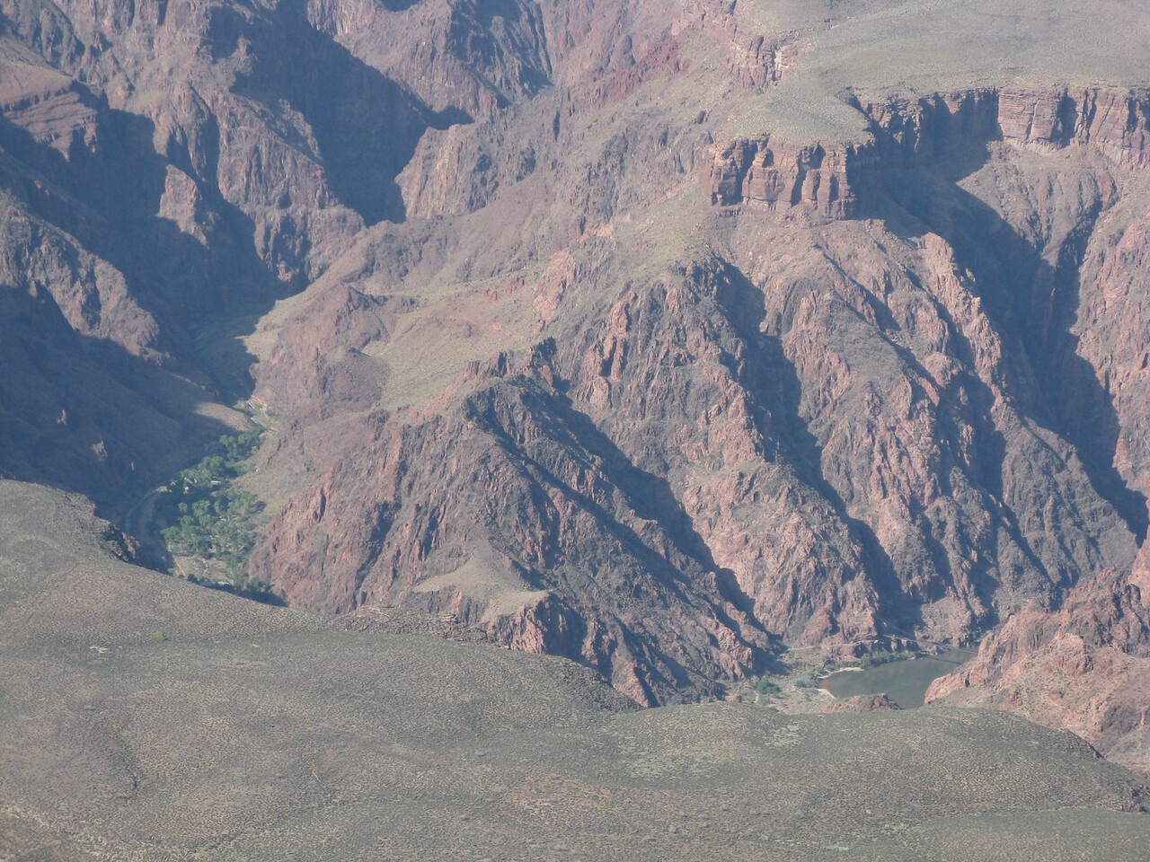 The Colorado River is seen in the right lower side of the picture.  Enlarge the picture a few times, and the Black Bridge, with the trail approaching it, becomes visible above the river.  On the left side of the picture is Phantom Ranch.  The green cottonwood trees are a distinct contrast to the rest of the arid landscape.