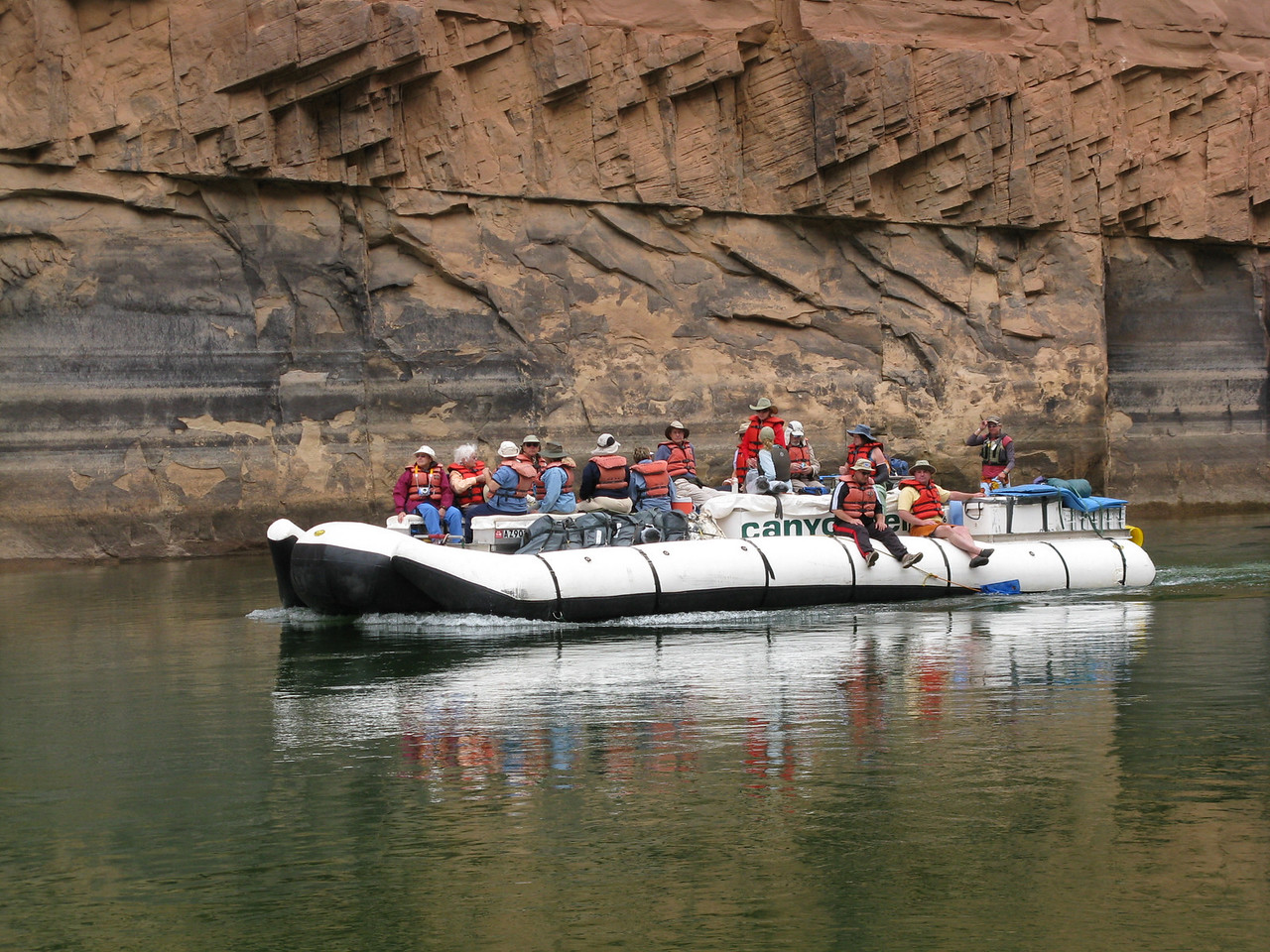 A Canyoneers raft in front of a rock layer called Coconino Sandstone.