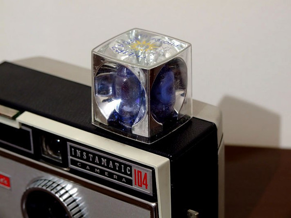 A flashcube mounted on a Kodak Instamatic film camera. Once the four flash bulbs were used, you threw it away.