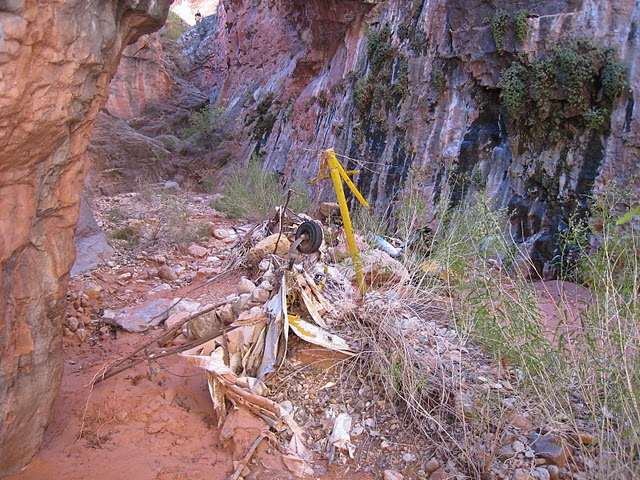 """THE CRASH SITE - MARCH 2011<br /> <br /> Since the accident, the wreckage of """"N6566H"""" has settled at the bottom of the canyon partially covered by sand and silt from seasonal flash floods.<br /> <br /> For the visitor, these narrow notch canyons offer little escape during flash floods and can be deadly. Consideration of the weather is a must when visiting sites in these areas."""