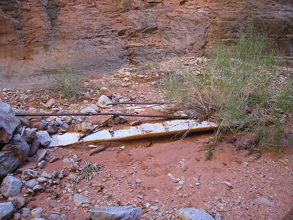 A section of the aircraft's right wing and support strut is almost completely buried under washed down sand and rocks.