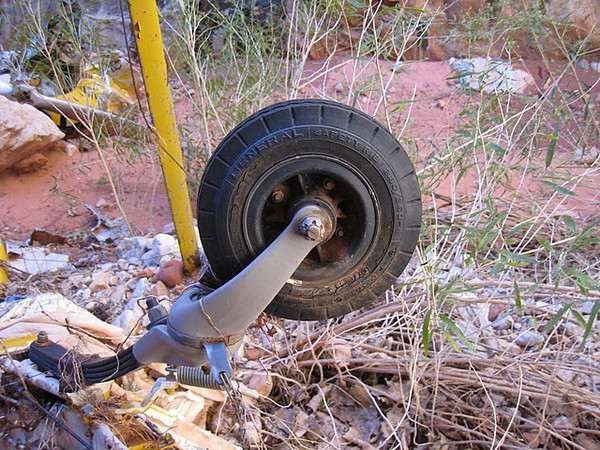 The tail wheel and tire assembly is one of the few components that appears to have survived the accident undamaged.
