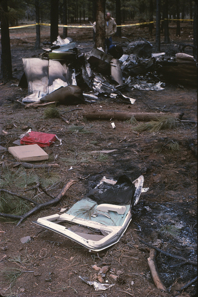 The right rear passenger door with the interior handle still in the closed and locked position lies amid other debris.