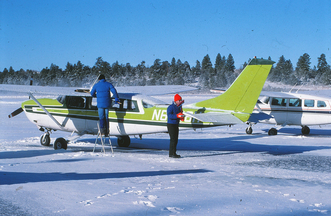 "January was one of the coldest months of the winter of 1990-1991 with temperatures often dropping below zero degrees Fahrenheit. <br /> <br /> It was a daily job for the winter season tour pilots to remove the loose snow from the aircraft's wings and tail surfaces. AGC Pilots Scott Featherstone and Paul Richfield seen here cleaning up ""Adventure One""."