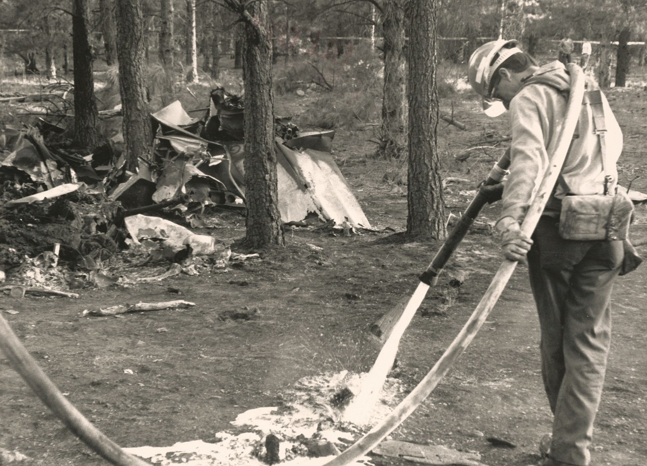 A firefighter from the U.S. Forest Service extinguishes a hotspot at the impact site.