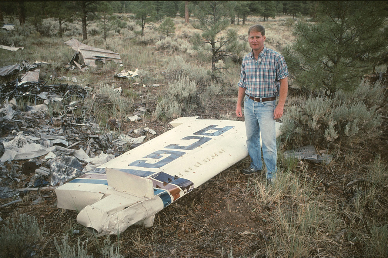 """In this 1990 photo, Paul Richfield, a pilot for air tour company Air Grand Canyon stands next to the vertical stabilizer of """"Canyon 6"""". <br /> <br /> The rudder and horizontal stabilizer were virtually undamaged during its separation and free-fall into the canyon. (1990 LostFlights)"""