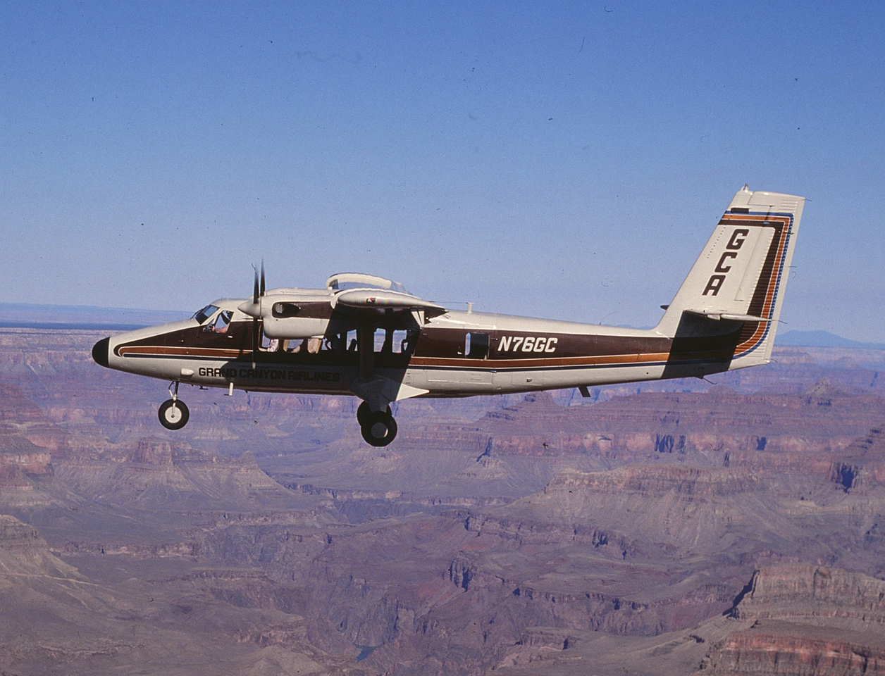 """Twin Otter """"N76GC"""" seen here in a promotional photo over the canyon was the first Twin Otter """"Vistaliner"""" to be delivered to Grand Canyon Airlines.<br /> <br /> To offer the passengers a slow, comfortable ride over the canyon, the pilots would normally fly the air tour at around 90 knots indicated air speed with the wing flaps extended to 10 degrees."""