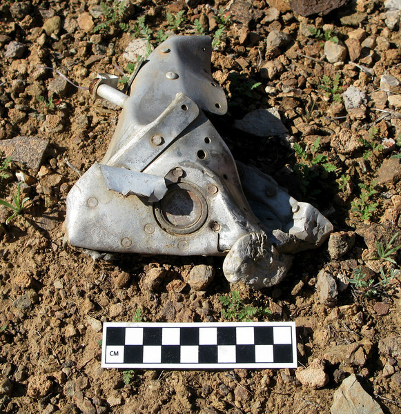 """A fire damaged fragment of the Twin Otter's engine nacelle was identified by the round fire bottle disc indicator. It was located 480 feet from the """"Canyon 6"""" main impact site.<br /> <br /> A burned and melted fragment so far from the impact site puzzled me at first since the accident investigation revealed there was no fire at the time of collision. <br /> <br /> It was surmised that the fragment most likely fell to this location as the aircraft wreckage was being removed by helicopter during salvage operations."""