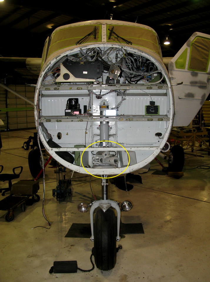 With the aircraft radome removed during maintenance, this photograph of a Nose Wheel Steering Actuator (circled) illustrates it's location on the Twin Otter.