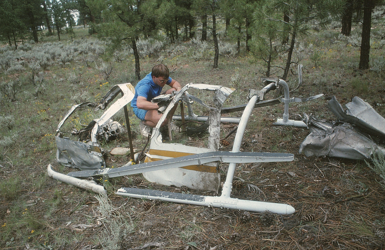 """THE RE-CONSTRUCTION OF """"TECH 2""""<br /> <br /> There were enough fragments of the helicopter lying around that a partial re-construction was possible. <br /> <br /> From the upper bends in the doors and minimal damage to the landing skids, it was becoming obvious that the helicopter had also impacted in an inverted attitude. (1990 LostFlights)"""