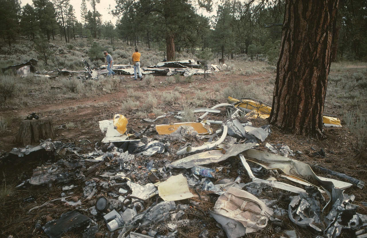 THE WRECKAGE DUMP SITE - 1990-1992<br /> <br /> The NTSB and other officials conducted their initial on-site investigation in the canyon. <br /> <br /> Once completed, the wreckage debris from both helicopter and airplane impact sites were removed from the canyon by helicopter and brought to this site on the canyon's south rim near the town of Tusayan, Arizona. <br /> <br /> In the foreground are the remains of the Bell 206B helicopter. The wreckage of the Vistaliner is piled in the background. (1990 LostFlights)