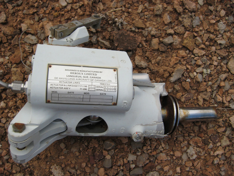 """Canyon 6's"" Nose Wheel Steering Actuator was discovered near the Tuna Creek drainage by a hiker in 2006.<br /> <br /> The presence of the hydraulic actuator in the debris field gives a clear idea of the severe damage inflicted by the helicopter's main rotor blades. <br /> <br /> The entire nose landing gear and wheel assembly of ""Canyon 6"" was sheared off the aircraft during the collision. Apparently the actuator was pulled out with it. (Photo courtesy of Larry Antonelli)"