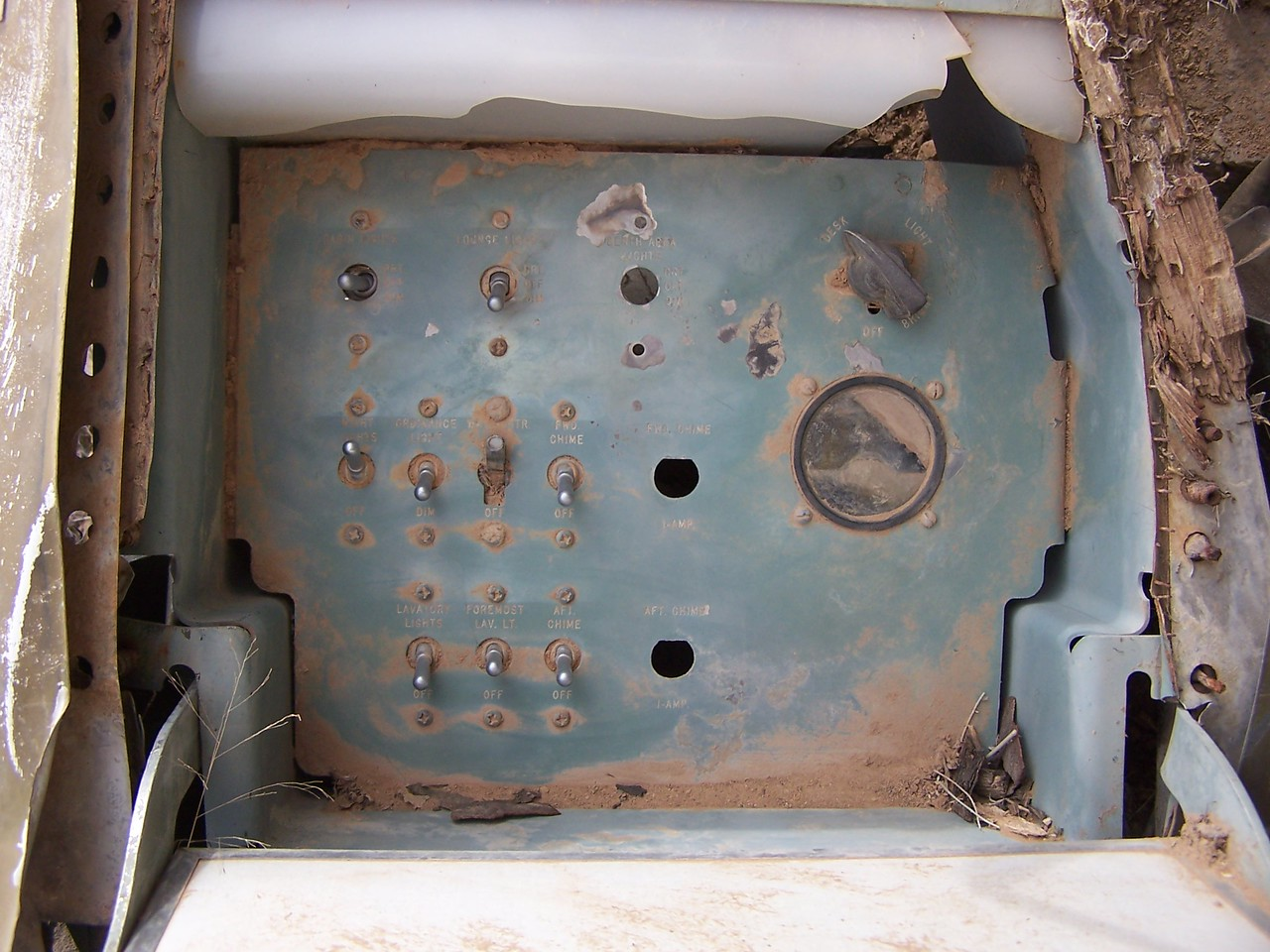 Closeup of the cabin bulkhead switch panel. Contains the flight attendant's (Hostess) aircraft cabin switches and controls for lighting, audible chimes, and cabin announcements. <br /> <br /> This bulkhead was located to the right of the main cabin entrance door.
