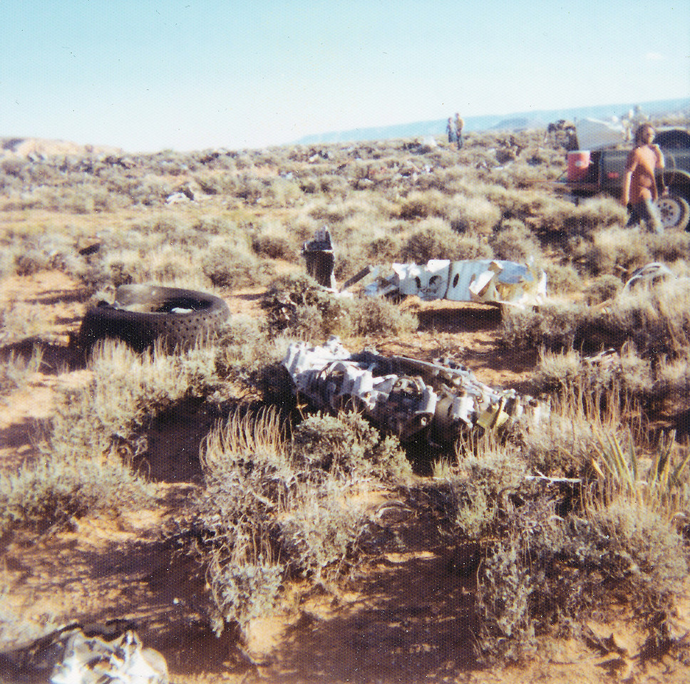 An engine and tire are some of more recognizable parts laid out for removal and salvage. (1976 NPS Photo)